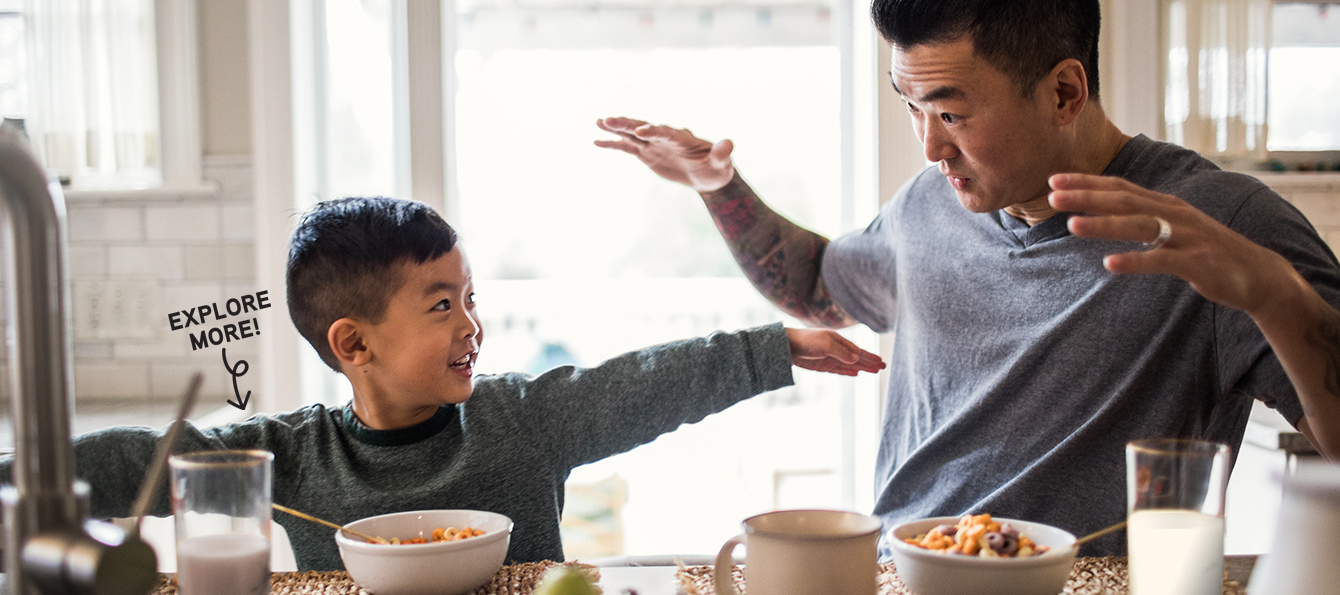 Father and son enjoying cereal with milk
