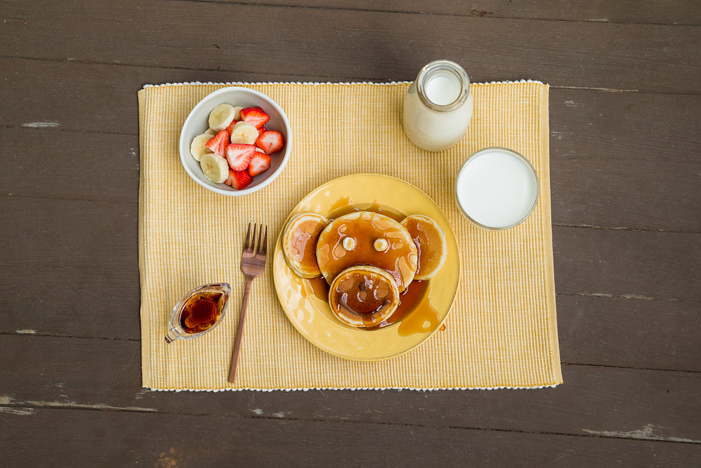 Plate of pancakes, fruit and a glass of milk.