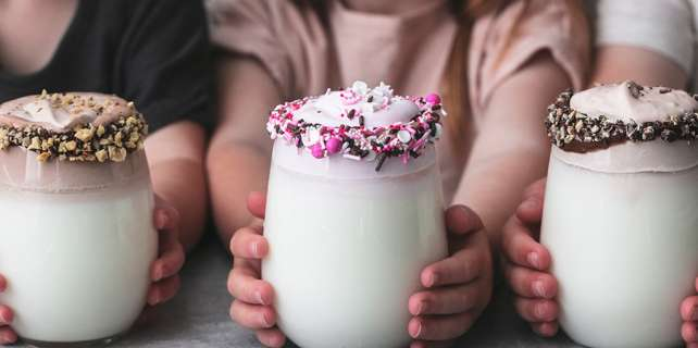 Children holding three different flavors of whipped milk